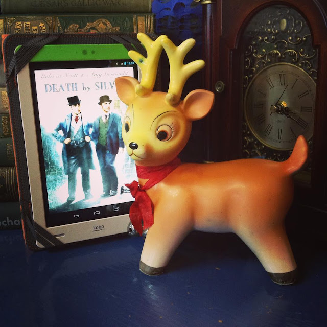 The world's angriest Christmas ornament stands next to a white Kobo with the cover of Death By Silver on it. The cover features two white men in Victorian dress. The ornament is a fat reindeer with a red bow and two silver bells around his neck. His mouth is severely downturned and his eyebrows arch high onto his forehead above very round eyes. He looks like he's never been impressed with anything in his entire life.