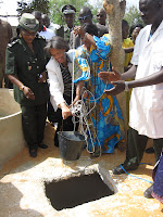 US Ambassador to Senegal Marcia S. Bernicat and Tostan Supervisor Aïssatou Kébé pull out the first bucket of water from the new well at Hann youth prison. The well will provide detainees with water for washing and benefit the agricultural training program initiated by Tostan.