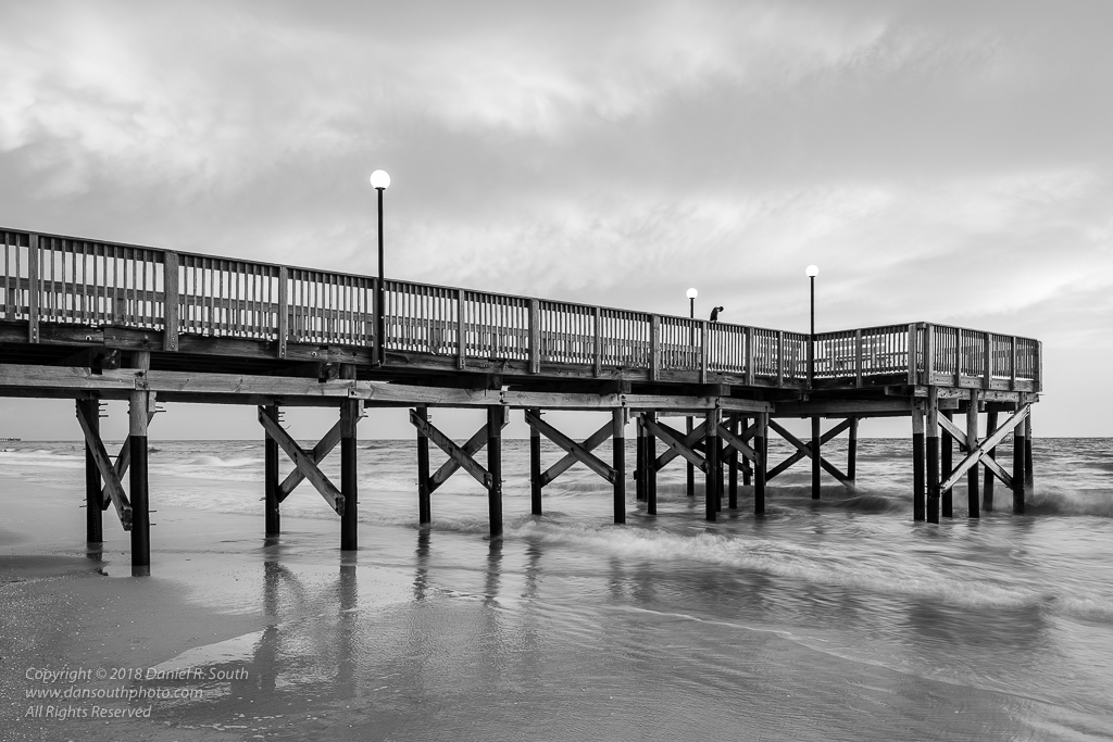 a photo of a fishing pier on a florida beach in black and white