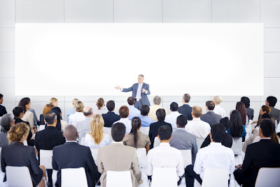 A presenter faces a large audience