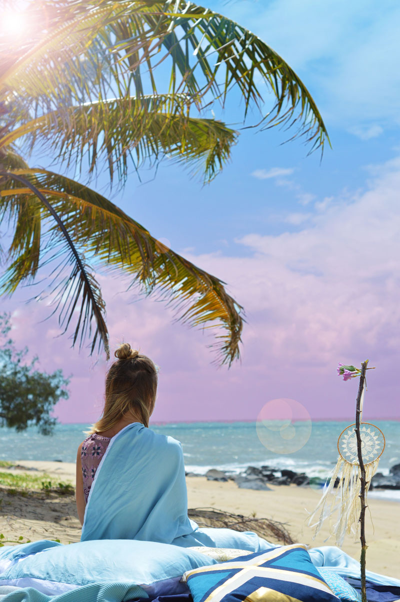 girl in pastel blue bedding under palm tree on far north queensland beach watching sunrise over sea