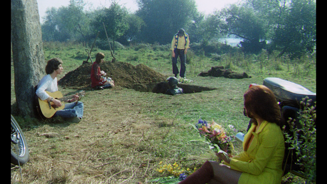 a group on hippie bikers sit around as their dead friend sits in his grave