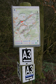 """Eine kleine Wanderkarte ist an einem Holzpfeiler befestigt. Darunter hängen zwei Schilder mit der Aufschrift """"A3"""", das untere der beiden weist darauf hin, dass es sich um einen Alternativweg handelt."""