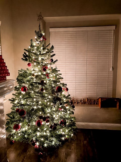 Christmas Tree With Gold Twinkle Lights and Red Ornaments Next to Fireplace