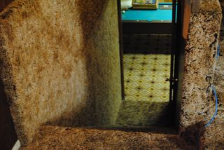 An inside image of a house with brown carpet everywhere