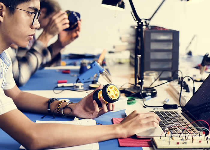 Sala com pessoas desenvolvendo projetos de robótica no movimento Make - Fab labs