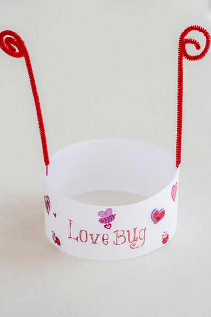 White construction paper headband hat with red writing, red pipe cleaner antennae, and stickers, paint, for decorations