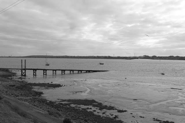 Looking into the Wyre Estuary - a wooden pier slopes into the water and a couple of sailboats are moored off shore.