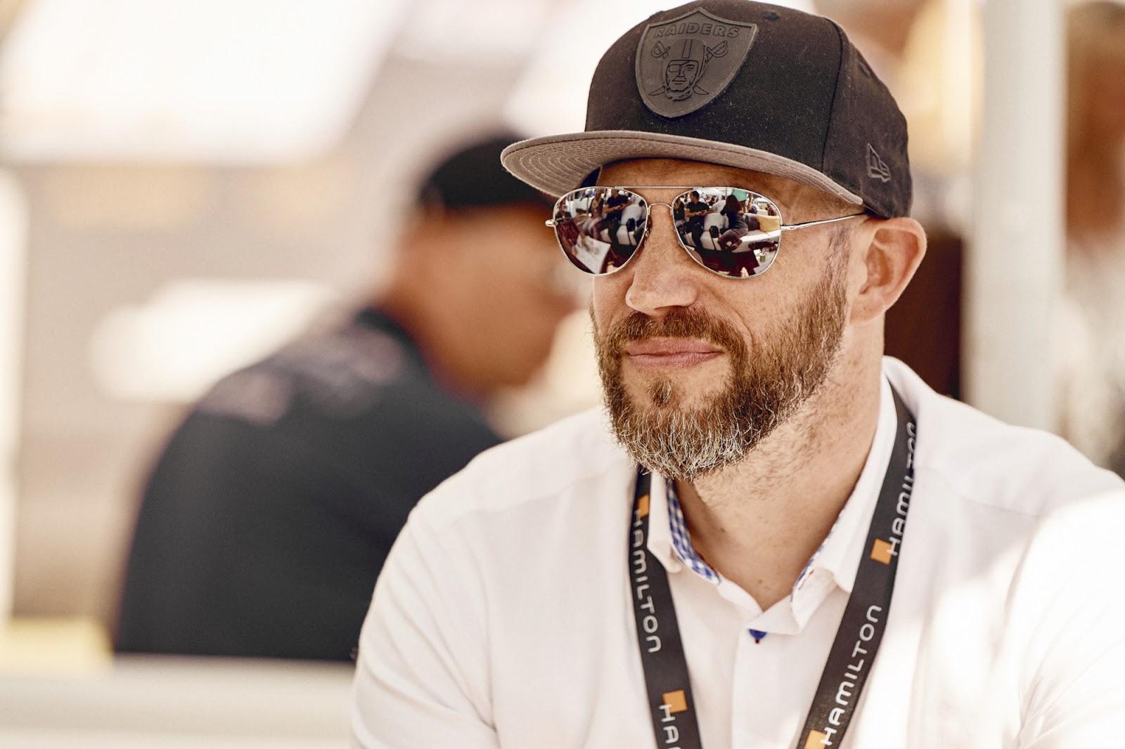 Der Blogger Jens Mahnke in der VIP Sky Lounge am Lausitzring mit Sonnenbrille und Kappe auf. Um den Hals ein Hamilton Keylace