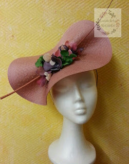 tocado grande en rosa nude con pluma y flores pequeñas de colores