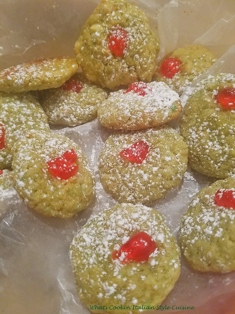 these are a festive macadamia nut green cookie with cherries on top with the elf on the shelf female doll in the photo along with pine cone centerpiece. for the Christmas cooking tray and baking holiday season