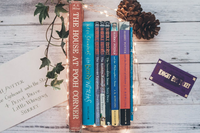 A series of books surrounded by fairylights and ivy including The House at Pooh Corner by A.A Milne, The Belfry Witches by Kate Saunders, the Horrible History books by Terry Deary, Harry Potter by J.K Rowling and The Invisible Dog by Dick King-Smith