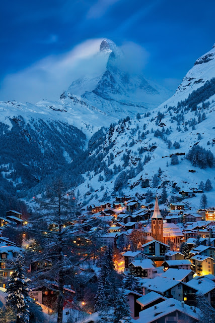 Close-up view of Zermatt aglow by the village lights with the imposing Matterhorn rising in the background.