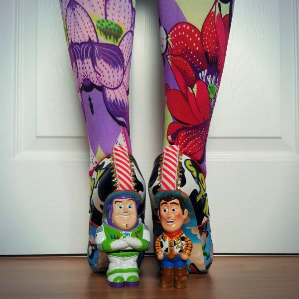 back view of legs in floral tights with Buzz and Woody Disney Toy Story character heels
