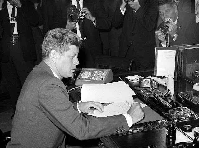 President Kennedy is surrounded by photographers as he sits at his desk in the White House, on October 23, 1962, shortly after signing a presidential proclamation concerning the Cuba Missile crisis.