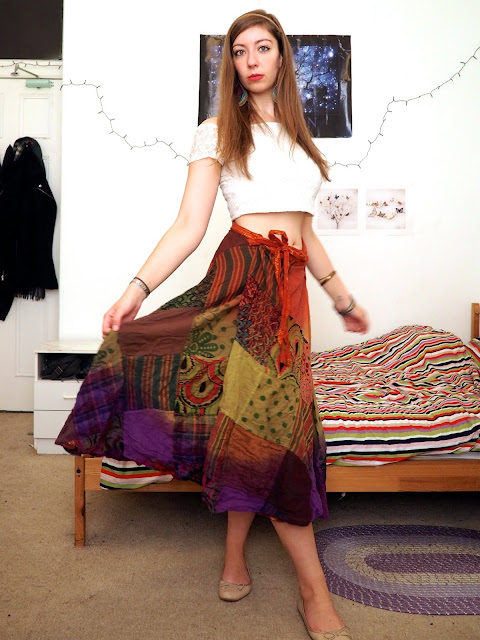 Esmeralda Disneybound outfit of white off the shoulder crop top, long rainbow pattern skirt, nude flats & bold jewellery