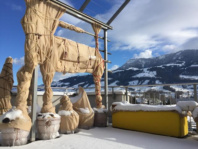 Linke Balkonseite mit Schnee und eingepackten Pflanzentöpfen