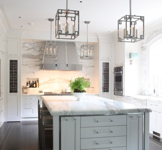 kitchen with marble cabinets, an island, detailed upper cabinetry, a stainless hood and lantern pendant lights