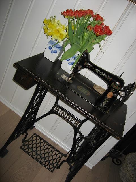 Uvanlige vaser til påskens blomster - Gamle krukker til tulipaner og narsisser, stående på et Singer symaskinbord