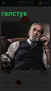 Мужчина в кресле в жилетке с галстуком и сигарой в руках с сердитым выражением лица
