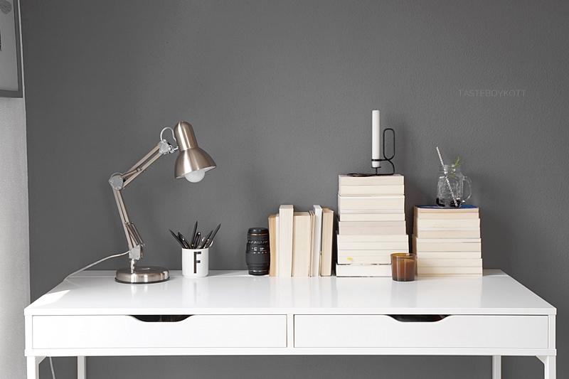 Schreibtisch dekorieren mit umgedrehten Bücherstapeln, Kerzen, Leuchte in schwarz, weiß, grau, natur, braun | Tasteboykott
