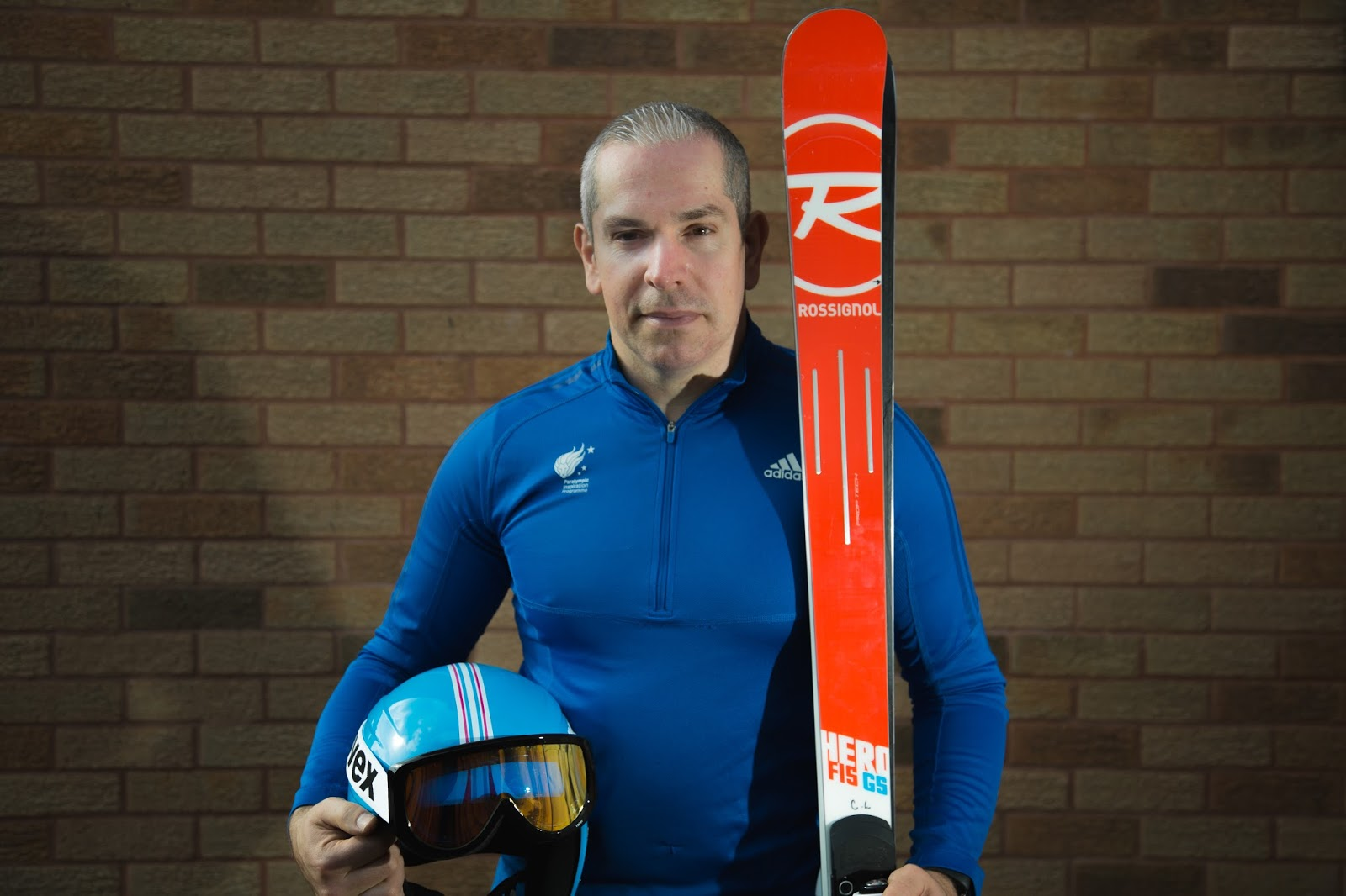 Man is looking at the camera wearing a blue ski suit, holding a blue helmet and red skis.