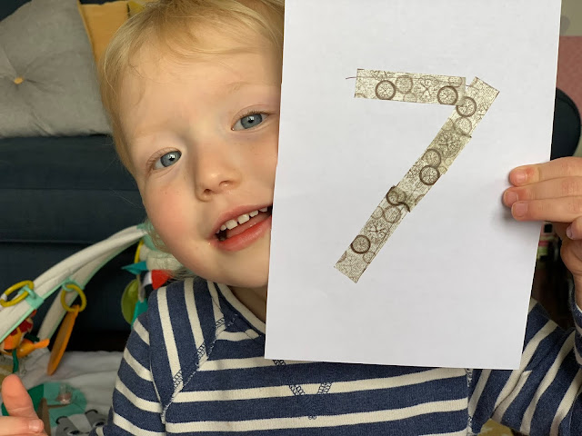 Toddler holding up a sheet of paper with the number 7 covered in washi tape