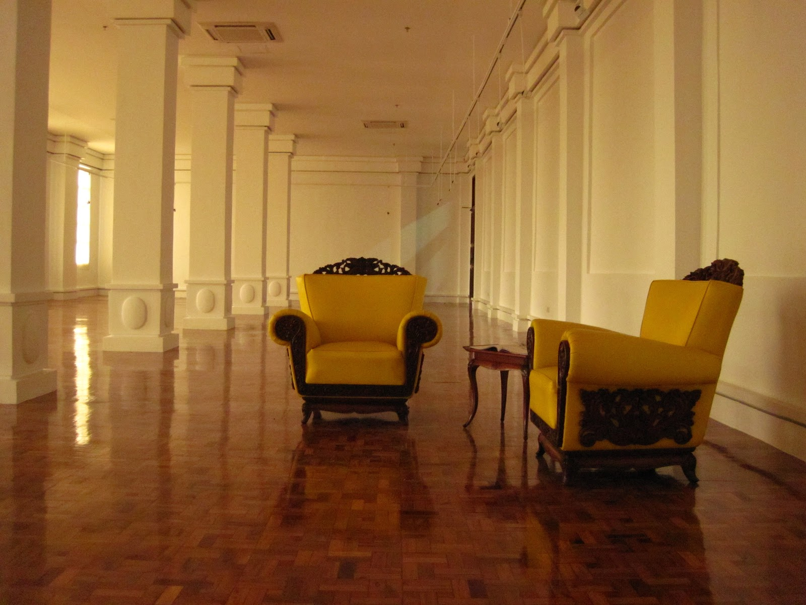 Two yellow chairs in empty gallery hall. (Photo by Bernard Eirrol Tugade)