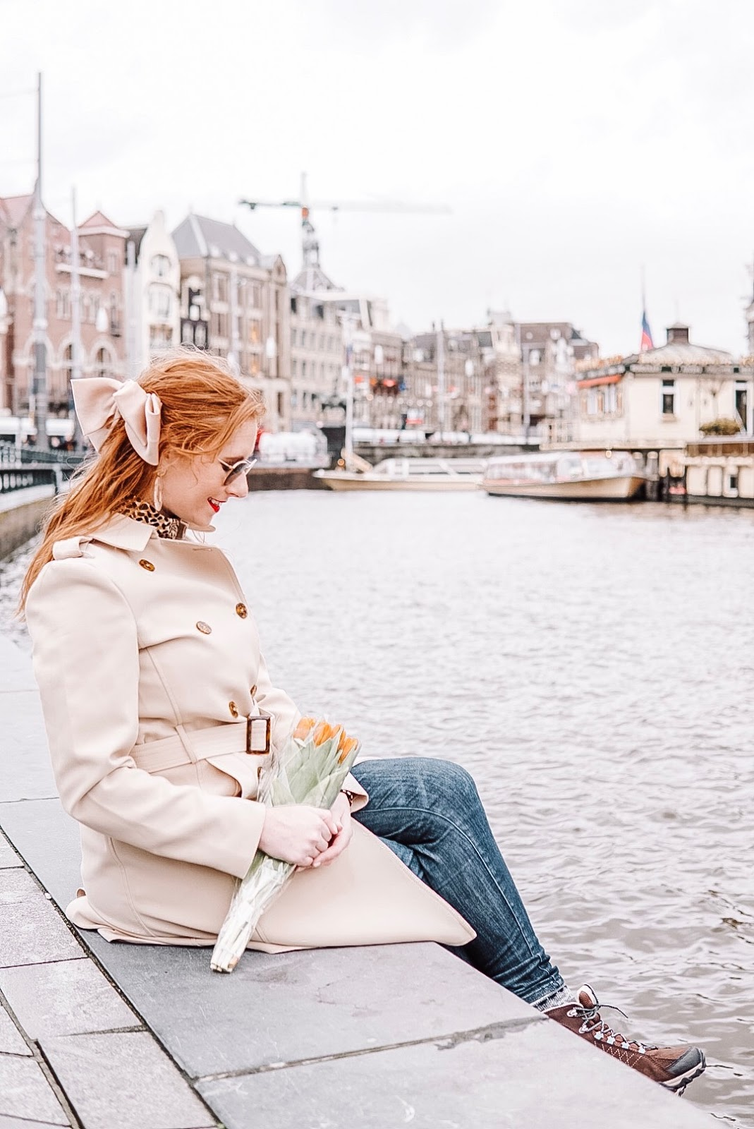 tampa blogger amanda burrows is in amsterdam. she is sitting along the canal. she is wearing a tan trench coat and holding orange tulips.