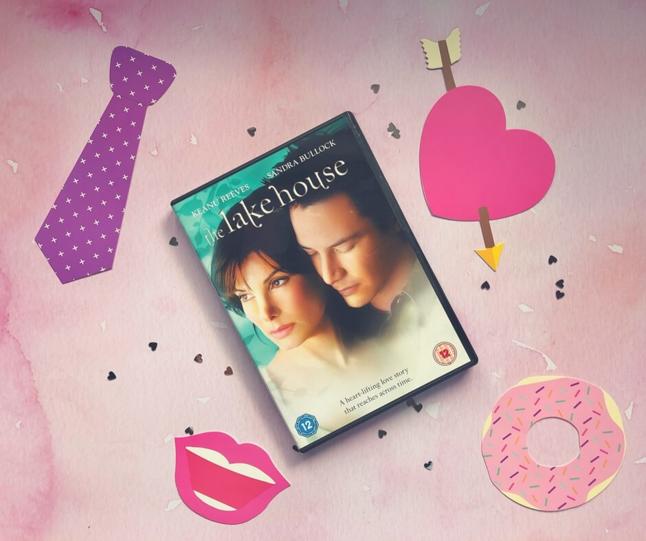 The Lake House DVD sits on a pink background surrounded by small silver hearts. In the top right corner is a pink heart with an arrow through it. In the bottom right is a picture of a doughnut with pink icing and sprinkles. In the bottom left corner is a picture of a smiling mouth with pink lips. In the top left corner is a purple tie.