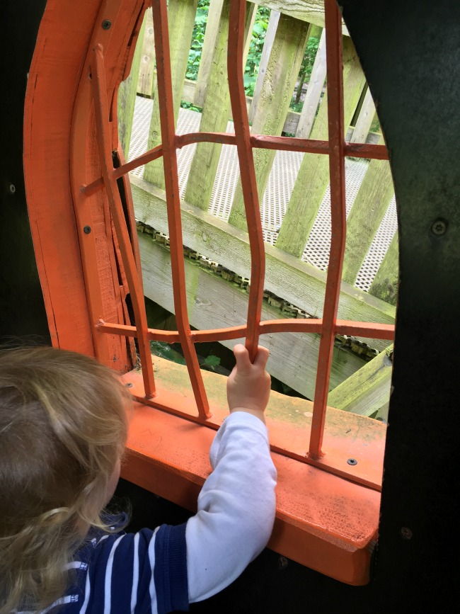 toddler-looking-out-of-wiggly-crooked-window-at--Perrygrove-Railway-adventure-playground