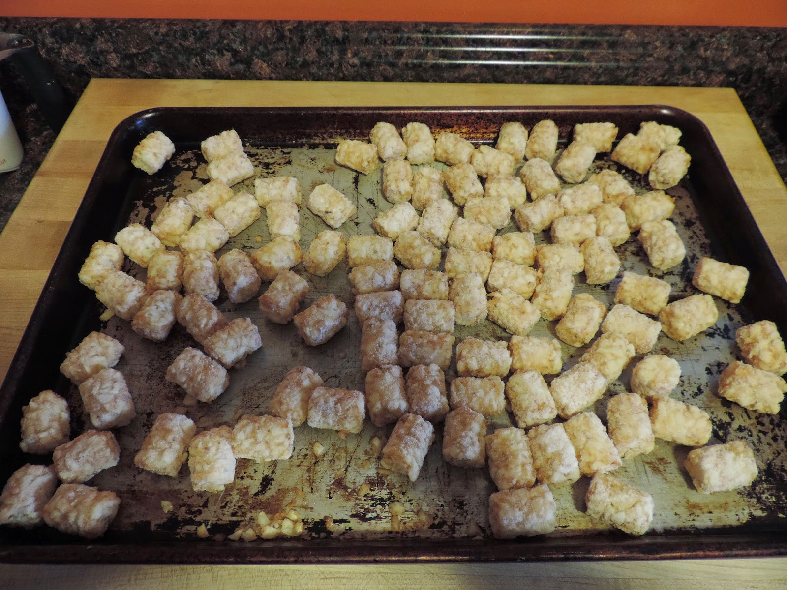 Frozen tater tots on a baking sheet.