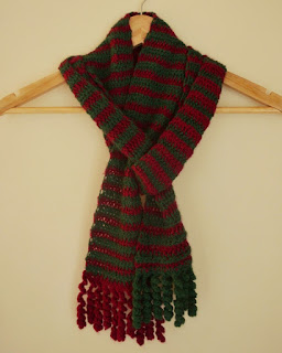 The scarf is hanging on a wooden triangular coathanger as if it were draped around someone's neck. The ends are woven together to make a layered knot.