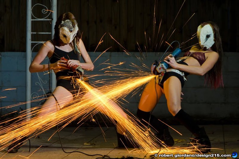 Two girls with owl masks, using metal grinders to make showers of sparks. Copyright 2012 Robert Giordano