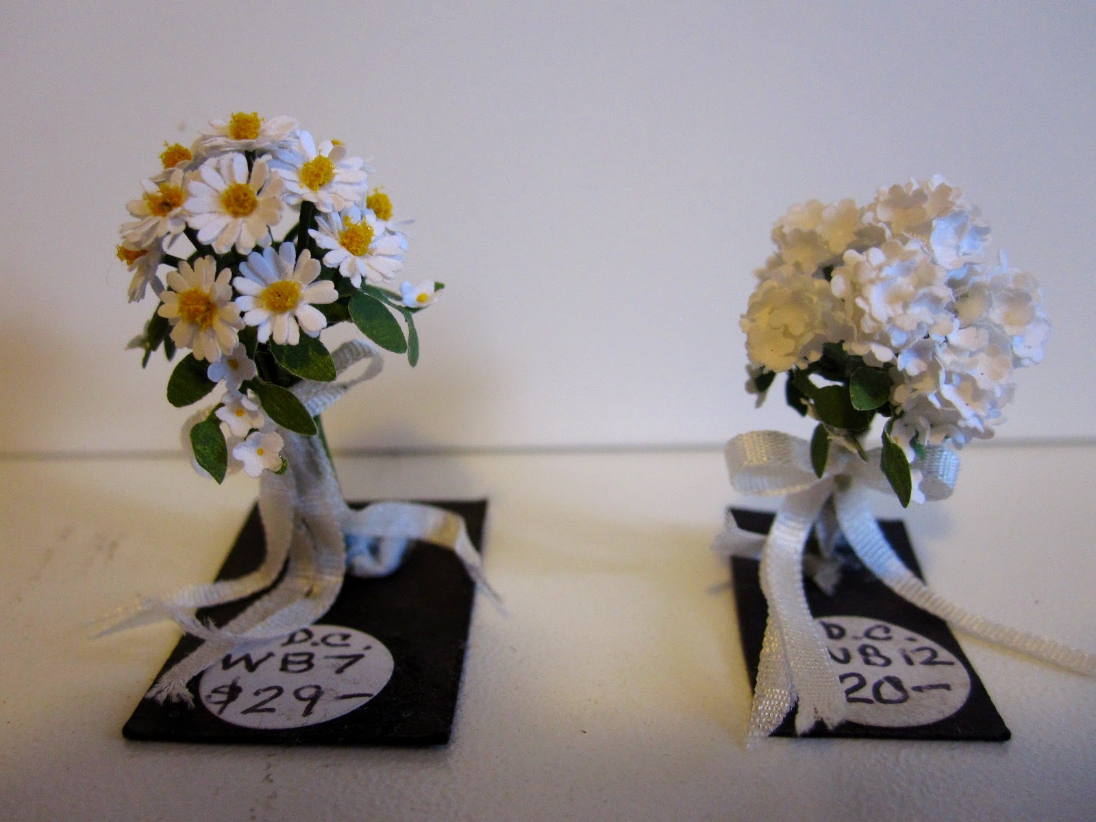 Two miniature posies of flowers: on the left is a bunch of daisies with a price sticker saying $29. On the right, a bunch of hydrangeas with a price sticker saying $20.
