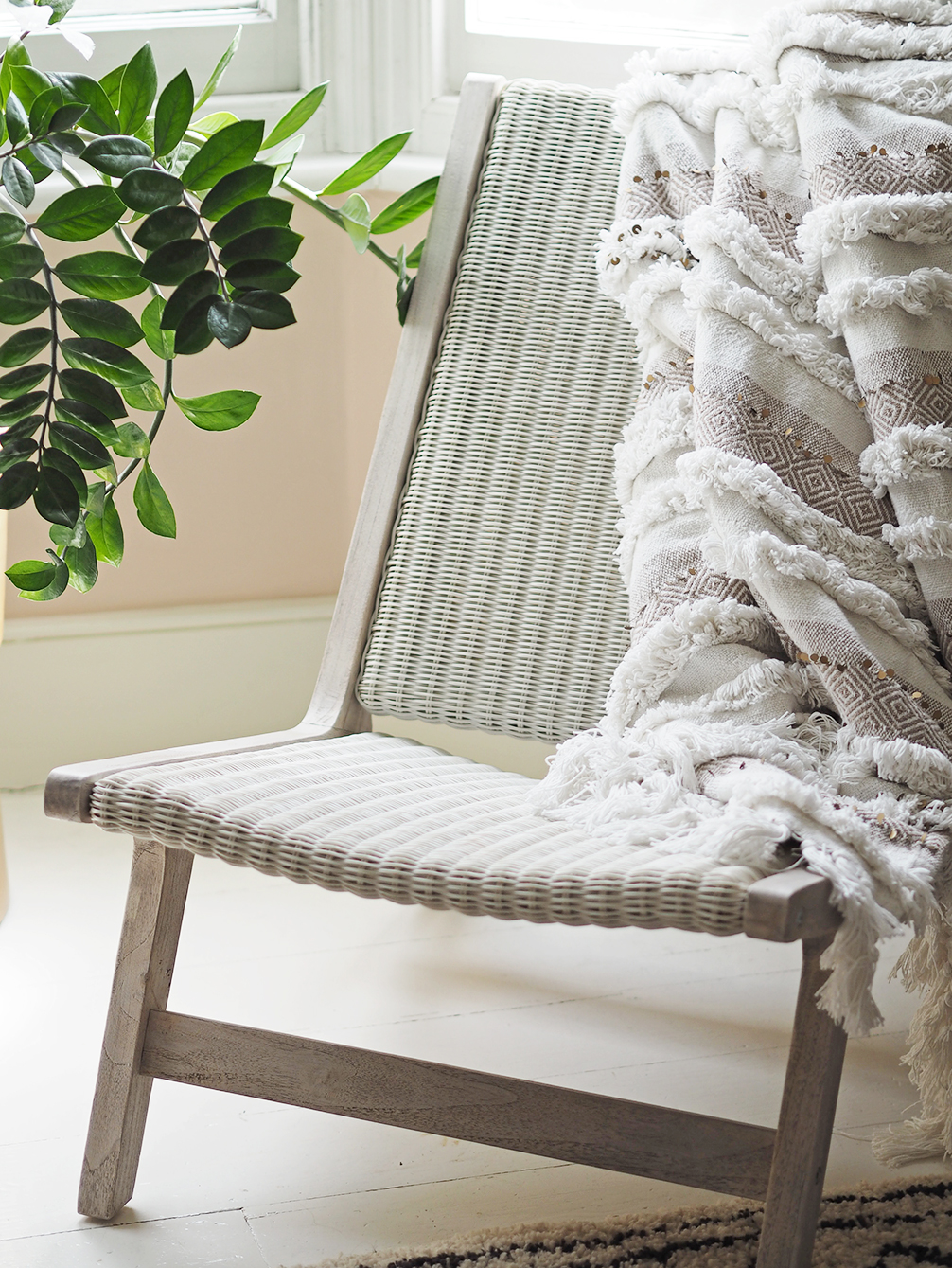 Outdoor Furniture Indoors - French For Pineapple Blog - close up of wicker and teak chair with moroccan throw and zz plant