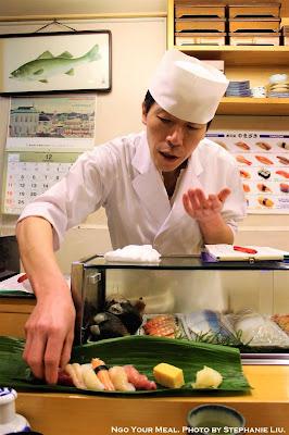 Chef placing sushi at Yamazaki in Tokyo, Japan