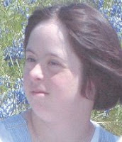 A headshot of a plump young white woman with short, dark hair gently blowing in the breeze, sitting in a field of bluebonnets