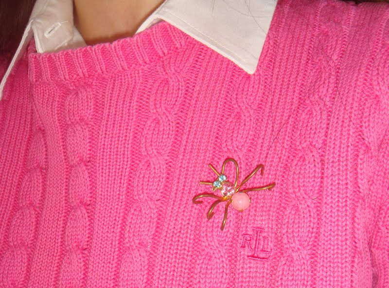 Up close of the spider brooch. Gold legs with 2 pink stones as body and blue stone eyes.
