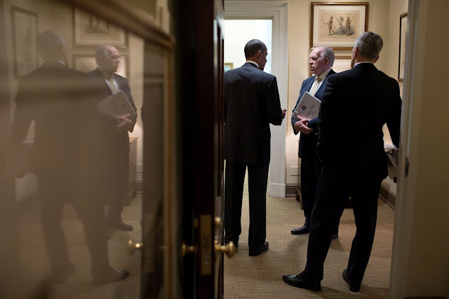 Image Attribute: U.S. President Barack Obama talks with CIA Director John Brennan (C), and Chief of Staff Denis McDonough in a West Wing hallway at the White House in Washington, DC, U.S. on May 10, 2013. Courtesy Pete Souza/The White House/Handout via REUTERS