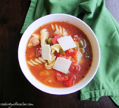 bow of tomato and pepper chicken and noodle soup with cheese on top