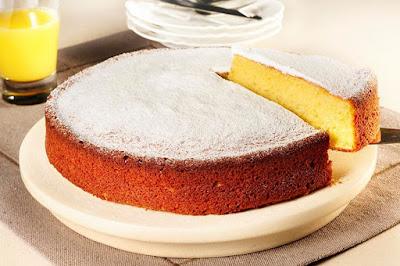 Imagem de um bolo simples e sem glúten com açúcar de confeiteiro polvilhado. Uma delícia