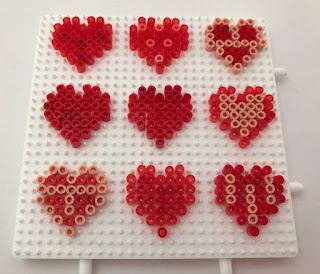 Mini Hama beads used to make hearts on peg board