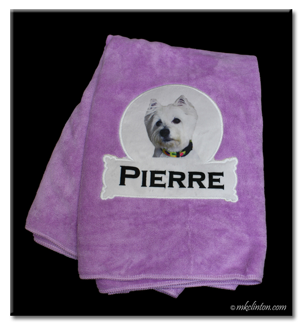 Purple towel from PrideBites with Pierre and Westie picture on it