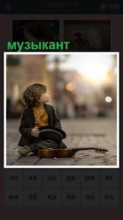 на мостовой сидит мальчик со скрипкой и шляпой