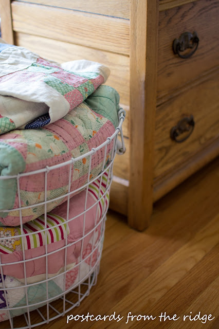 Pretty vintage quilts in a basket. So many great decorating ideas here. Postcards from the Ridge