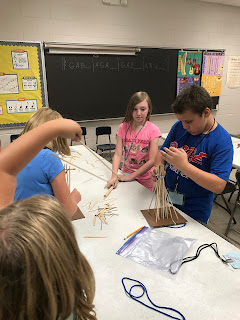 Students standing at a table working on windmills