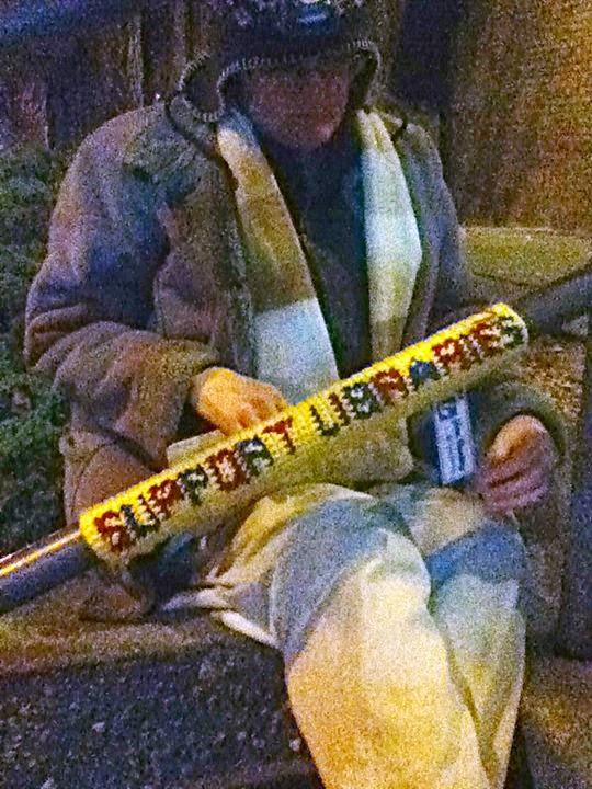 "Cynthia M. Parkhill attaches a length of crocheted fabric reading ""Support Libraries"" to railing outside Santa Rosa downtown library at night."