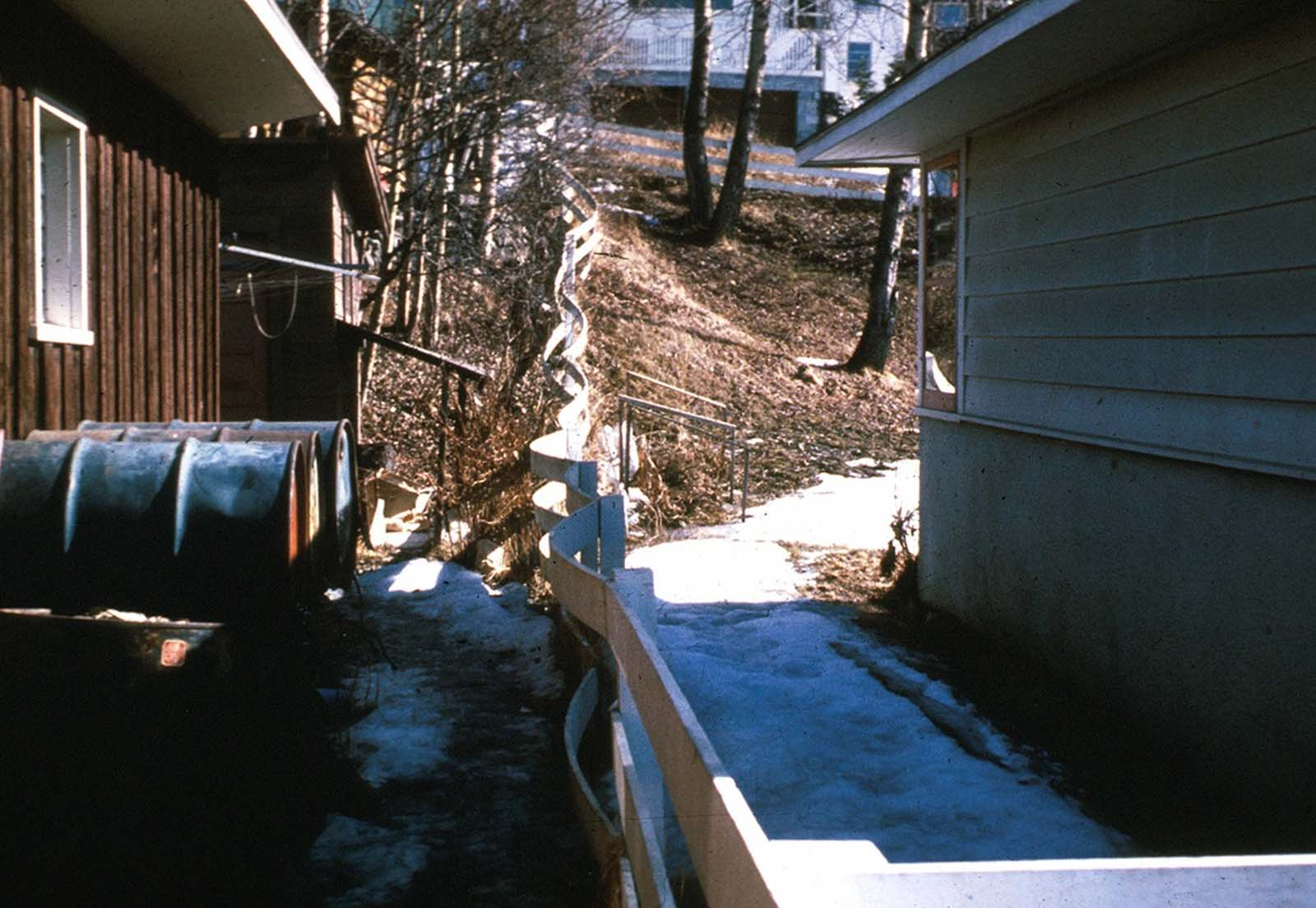 In an Anchorage neighborhood, a wooden fence at the toe of the L Street landslide, buckled and shortened by compression.