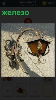 К стене прикреплен фонарь сделанный из железа с лампочкой внутри и вензелями вокруг